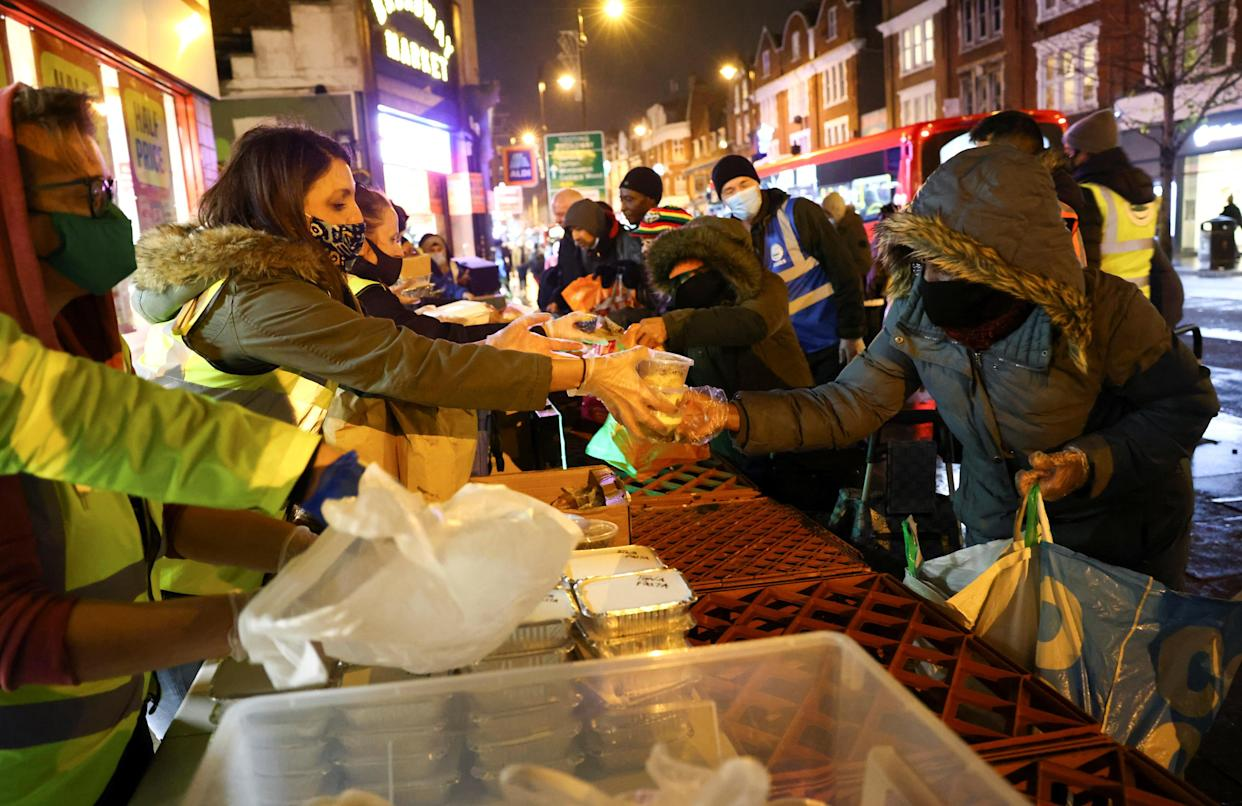 Volunteers working for the Tooting Community Kitchen hand out food donations to those in need, amid the coronavirus pandemic, in Tooting, South London, Britain, November 14, 2020. Picture taken November 14, 2020. REUTERS/Henry Nicholls