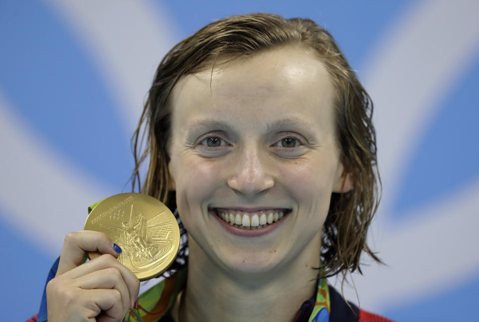 FILE - In this Aug. 9, 2016, file photo, United States' Katie Ledecky shows off her gold medal during the ceremony for the women's 200-meter freestyle final during the swimming competitions at the 2016 Summer Olympics, in Rio de Janeiro, Brazil. Ledecky is turning pro. The five-time Olympic gold medalist announced on Twitter that she is giving up her final two years of eligibility at Stanford, though she will continue to train at the West Coast school as she works toward her degree. (AP Photo/Michael Sohn, File)
