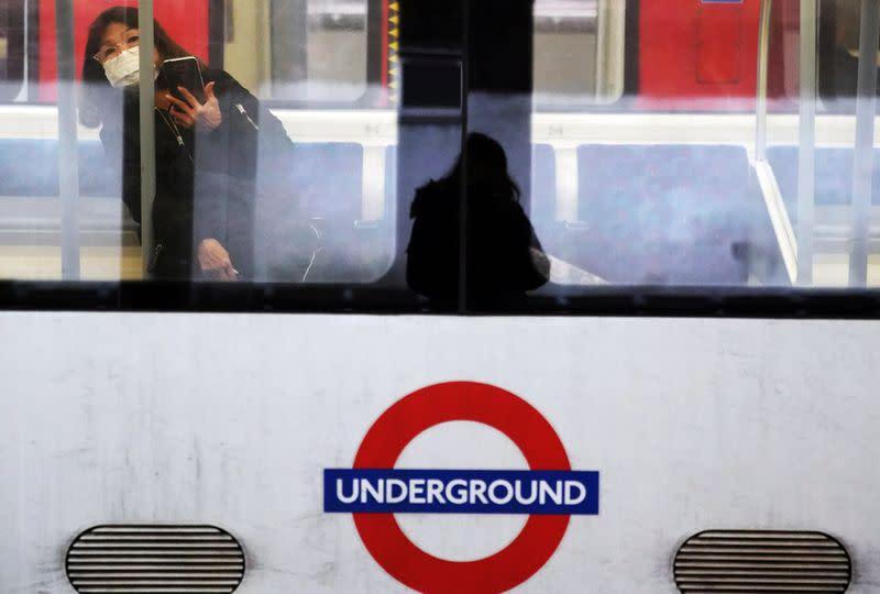 A woman wearing a protective mask travels on a Jubilee Line tube train in London