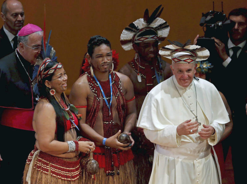 Pope Francis wears an indigenous headdress given to him by Ubirai Matos from the Pataxo tribe, fourth from left, after the pontiff spoke at Rio's Municipal Theater to an audience mostly made up of Brazil's political, business and cultural elite in Rio de Janeiro, Brazil, Saturday, July 27, 2013. Pope Francis is on the sixth day of his trip to Brazil where he will attend the 2013 World Youth Day in Rio. (AP Photo/Monica Imbuzeiro, Agencia O Globo)