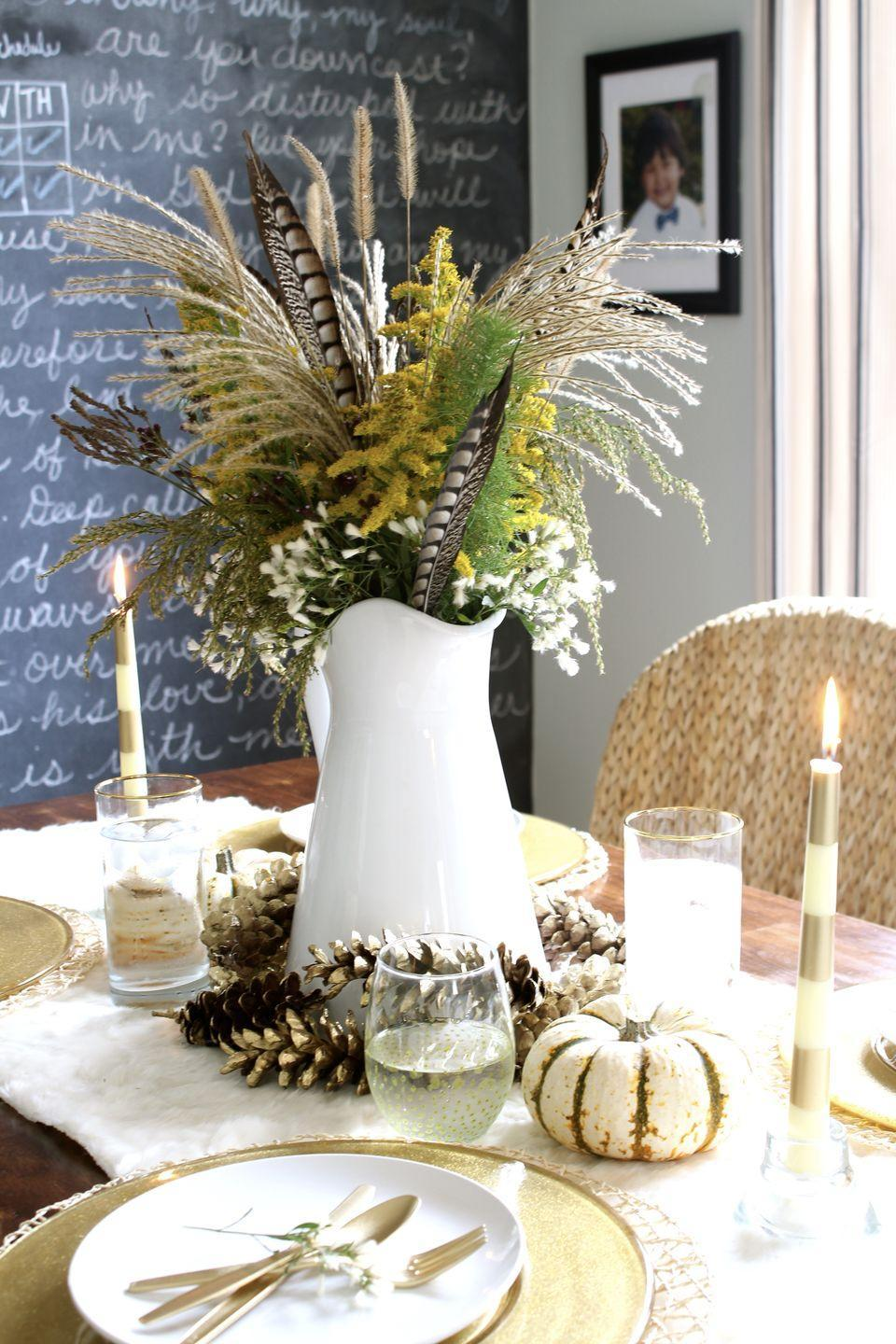 """<p>This dramatic fall table from <a href=""""http://simplestylings.com/blogger-stylin-home-tour-thanksgiving-edition-create-wildflower-centerpiece-sweet-potato-casserole-family-recipe/"""" rel=""""nofollow noopener"""" target=""""_blank"""" data-ylk=""""slk:Simple Stylings"""" class=""""link rapid-noclick-resp"""">Simple Stylings</a> includes an unexpected combination of pheasant feathers, pine cones, and white pumpkins. The hand-picked floral arrangement is surrounded by gold pine cones and styled on top of a <a href=""""https://www.elledecor.com/design-decorate/interior-designers/a9040/faux-fur/"""" rel=""""nofollow noopener"""" target=""""_blank"""" data-ylk=""""slk:faux-fur table runner"""" class=""""link rapid-noclick-resp"""">faux-fur table runner</a>.</p>"""