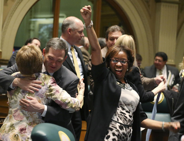 FILE - This May 8, 2013 file photo shows Rep. Rhonda Fields, right, pumping her fist at the conclusion of the legislative session in the House chambers. Fields was responsible for gun control laws being passed in Colorado. (AP Photo/Ed Andrieski, File)