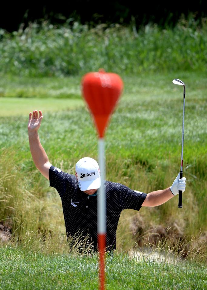 ARDMORE, PA - JUNE 14:  Graeme McDowell of Northern Ireland jumpes to avoid his golf ball in a greenside bunker on the 17th hole during Round Two of the 113th U.S. Open at Merion Golf Club on June 14, 2013 in Ardmore, Pennsylvania.  (Photo by Ross Kinnaird/Getty Images)