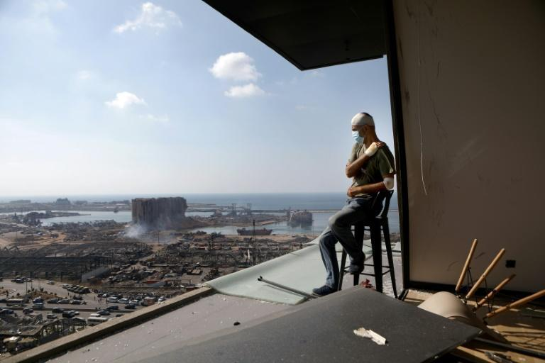 In this file photo taken on August 6, 2020 TV producer Tony Ahwaji sits injured on the balcony of his damaged apartment