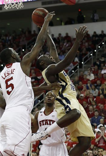 North Carolina State's C.J. Leslie (5) tries to block Georgia Tech's Mfon Udofia as North Carolina State's Lorenzo Brown looks on at rear during the first half of an NCAA college basketball game in Raleigh, N.C., Wednesday, Jan. 11, 2012. (AP Photo/Gerry Broome)