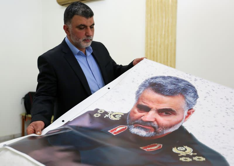A man holds a banner depicting late Major-General Qassem Soleimani, head of the elite Quds Force, who was killed in a U.S. airstrike Near Baghdad, at the Iranian embassy in Beirut