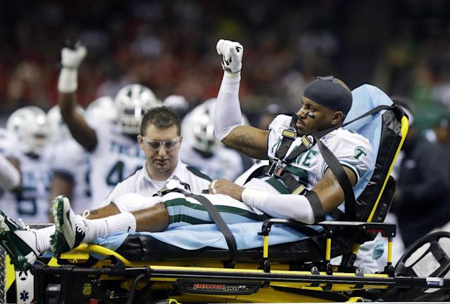Tulane cornerback Jordan Sullen waves to the crowd as he leaves the field after being injured against Louisiana-Lafayette during the second half of the New Orleans Bowl NCAA college football game, in New Orleans, Saturday, Dec. 21, 2013. (AP Photo/Bill Haber)