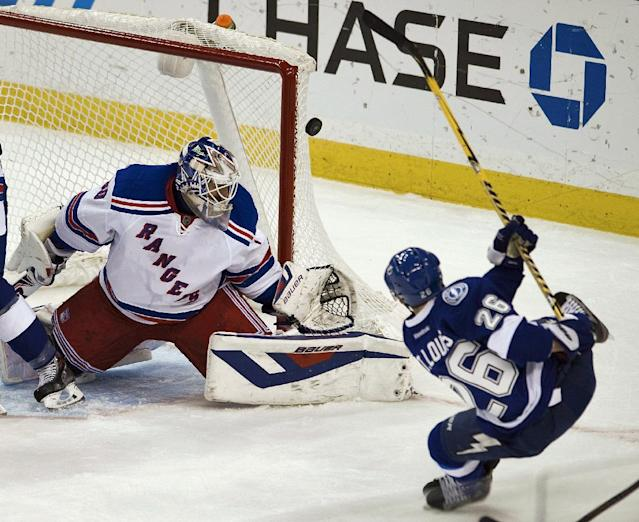 New York Rangers goalie Henrik Lundqvist (30) defends the net as Tampa Bay Lightning's Martin St. Louis (26) gets off a shot during the first period of an NHL hockey game, Sunday, Dec. 29, 2013, in Tampa, Fla. (AP Photo/Steve Nesius)