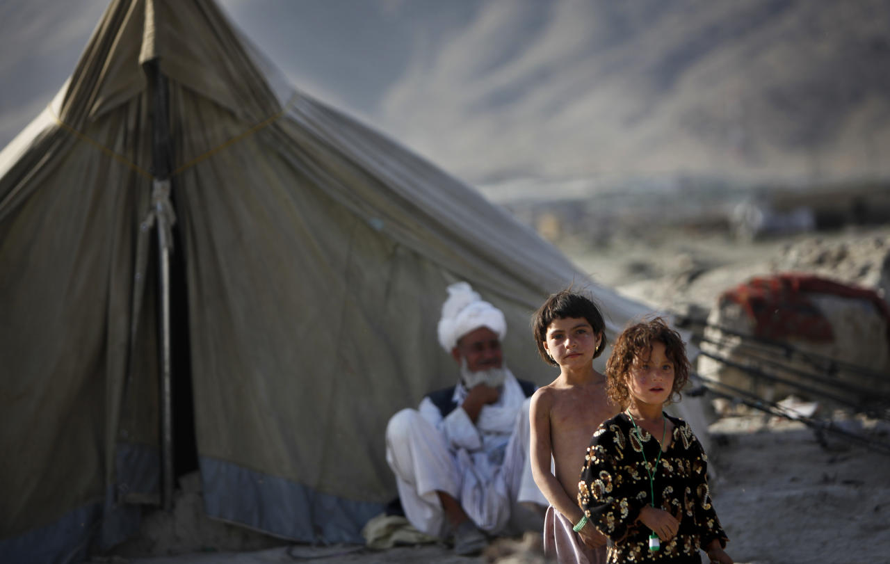 Internally displaced Afghan girls look on as a man rests in the shade of his makeshift tent at a camp for refugees in Kabul, Afghanistan, Monday, June 20, 2011. On World Refugee Day UN Refugee Agency (UNHCR) called for accelerated peace initiatives, so that all Afghan refugees can return, a statement of United Nations Assistance Mission in Afghanistan (UNAMA) said. (AP Photo/ Gemunu Amarasinghe)