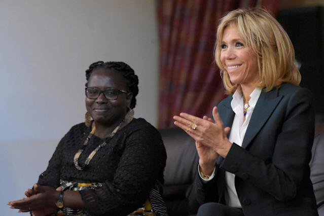 Brigitte Macron, wife of the French president, aplauds next to Catherine Sarr Sambou, director of Mariama Ba school on Goree island, once a west African slaving post, off the coast of Dakar, Senegal, February 2, 2018. REUTERS/Seyllou/Pool