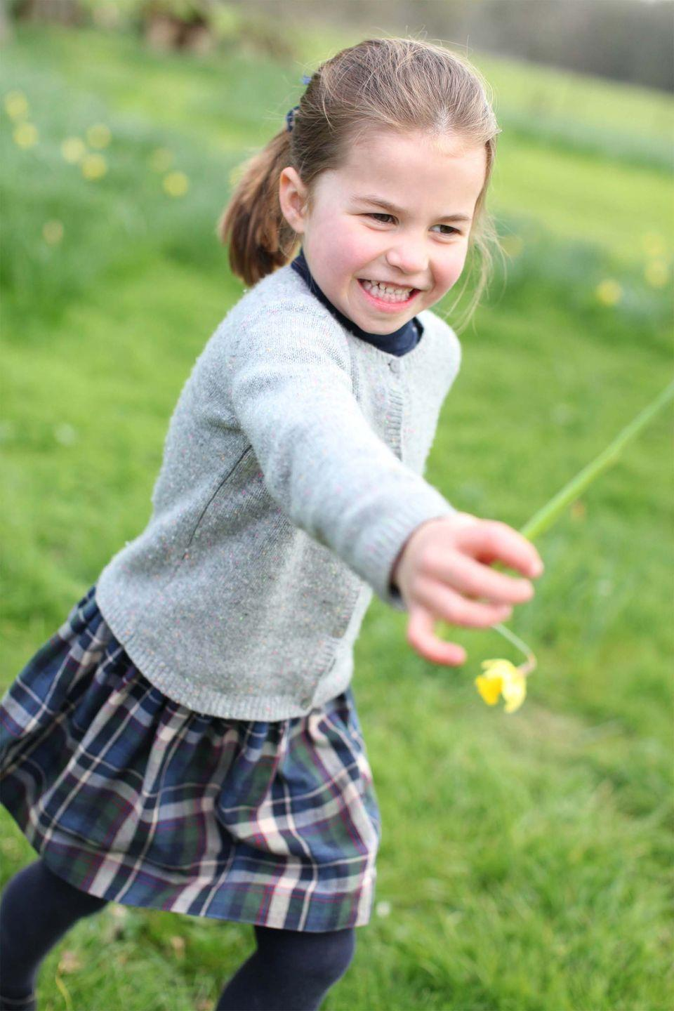 <p>The final photo shows Charlotte playing with flowers at the Cambridge residence in Norfolk.</p>