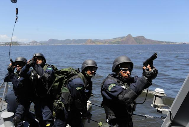 """CORRECTS WEDNESDAY TO THURSDAY - Brazilian Marines practice raiding a ship during a military exercise in Guanabara Bay, in Rio de Janeiro, Brazil, Thursday, Feb. 20 2014. Brazil's Navy said that the operations being carried out this week in preparation for the 2014 FIFA World Cup are the largest exercises in its history. FIFA director of security Ralf Mutschke has said that FIFA is satisfied with the level of security that will be provided by Brazilian authorities, and guarantees that football's governing body """"is highly committed to ensuring the safety and security for fans, players and any other stakeholder involved in our event."""" (AP Photo/Leo Correa)"""