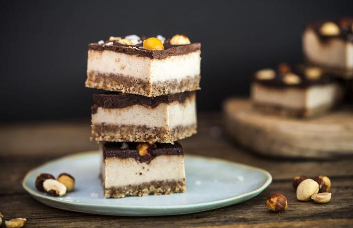 Slices of salted caramel and hazelnut slice, stacked ready to eat, scattered with whole nuts and salt flakes.
