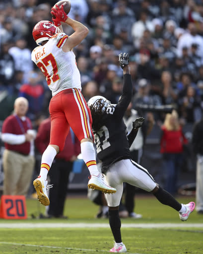 Kansas City Chiefs tight end Travis Kelce (87) catches a pass over Oakland Raiders defensive back Reggie Nelson during the second half of an NFL football game in Oakland, Calif., Sunday, Dec. 2, 2018. (AP Photo/Ben Margot)