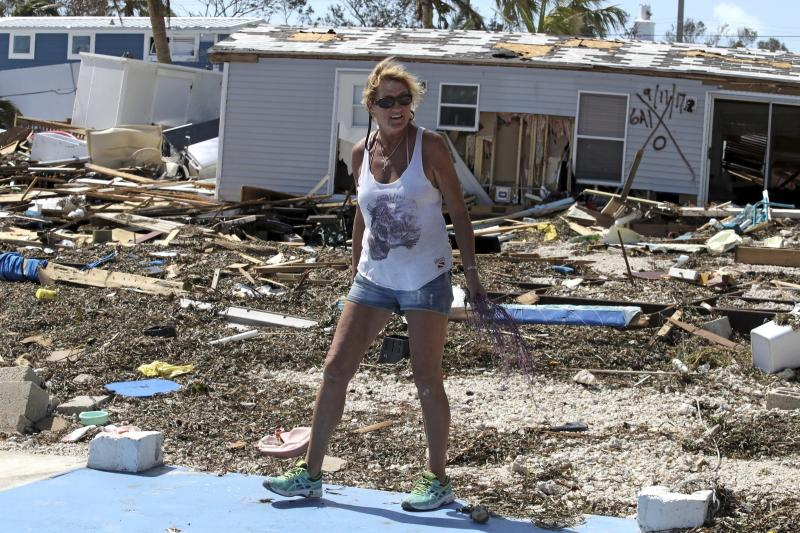Patty Purdo checks the damage at the Seabreeze trailer park along the Overseas Highway in the Florida Keys, Tuesday, Sept. 12, 2017. Florida is cleaning up and embarking on rebuilding from Hurricane Irma, one of the most destructive hurricanes in its history. (Al Diaz/Miami Herald via AP)