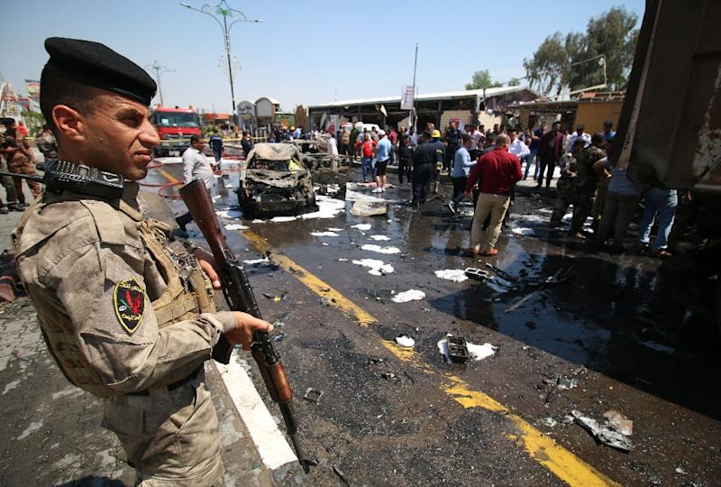 Iraqi security forces and emergency personnel gather at the site of a suicide attack in the southern port city of Basra on April 4, 2016 (AFP Photo/Haider Mohammed Ali)