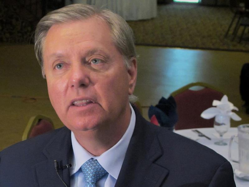 """FILE - In this Sept. 3, 2013 file photo Sen. Lindsey Graham, R-S.C. talks to a reporter following a speech in Goose Creek, S.C. The White House on Wednesday April 30, 2014 denied that a staff member's email three days after the deadly attack on the U.S. mission at Benghazi, Libya, was actually about the attack Graham, has called the email a """"smoking gun"""" that """"shows political operatives in the White House working to create a political narrative at odds with the facts."""" (AP Photo/Bruce Smith, File)"""