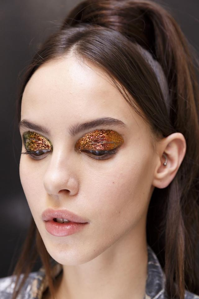 <p>Glittering, metallic eyeshadow appeared on the runways of Jean Paul Gaultier, Valentino, and Ralph & Russo. The lustrous look came in many hues, from ice blue to warm amber, adding a gleaming effect to models' eyes. Plus, the ultra-saturated application amplified the look that much more. </p>
