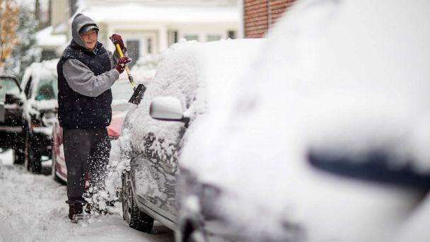 PHOTO: Benjamin Shoquette clears snow off his car outside his home, Dec. 3, 2019, in Providence, R.I. (David Goldman/AP)