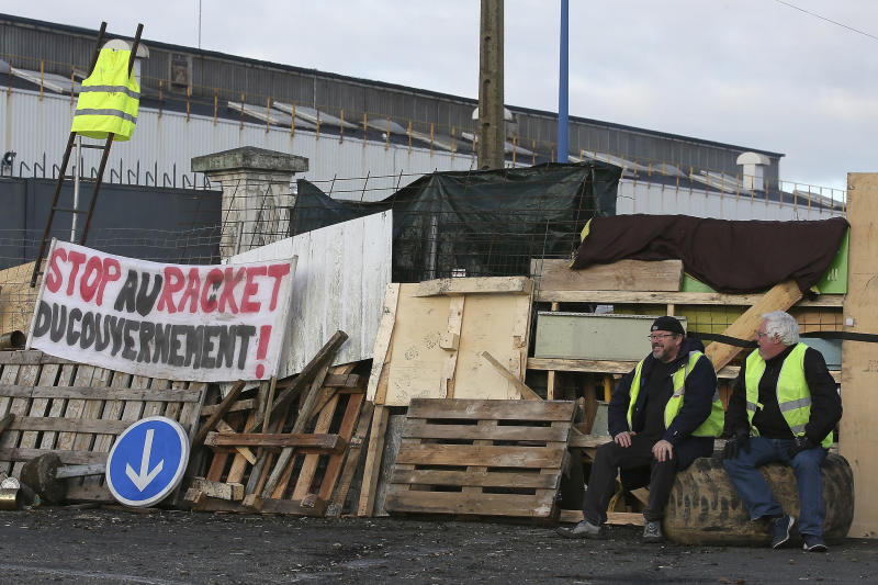 """Demonstrators sit in front of a makeshift barricade set up by the so-called yellow jackets to block the entrance of a fuel depot in Le Mans, western France, Tuesday, Dec. 5, 2018. Banner reads : Stop the Government racket. The French government's decision to suspend fuel tax and utility hikes Tuesday did little to appease protesters, who called the move a """"first step"""" and vowed to fight on after large-scale rioting in Paris last weekend. (AP Photo/David Vincent)"""