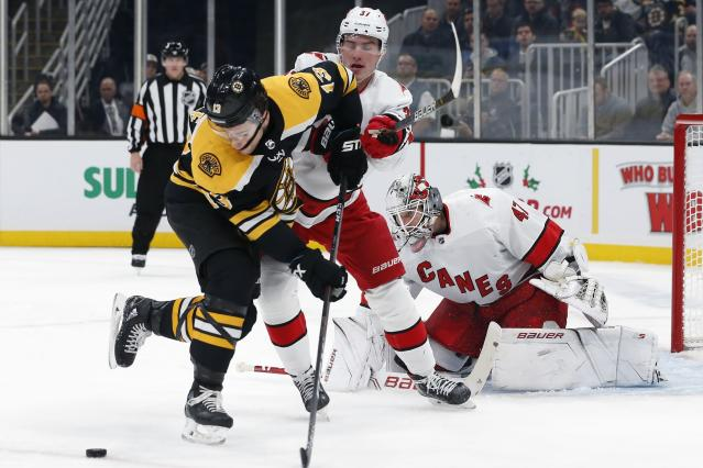 Boston Bruins' Charlie Coyle (13) tries to control the puck in front of Carolina Hurricanes' Andrei Svechnikov (37) and James Reimer (47) during the second period of an NHL hockey game in Boston, Tuesday, Dec. 3, 2019. (AP Photo/Michael Dwyer)