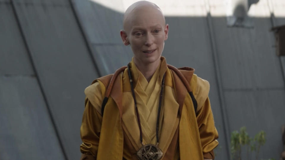 A woman in yellow robes, the Ancient One, looks curious
