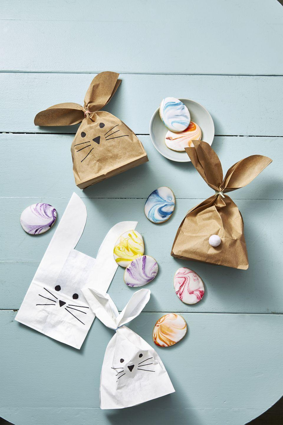 <p>Give everyone a to-go bag for any leftover desserts — and make them festive. Cut paper bags to make bunny-ear shapes, then draw on an adorable bunny face. Don't forget the pom-pom tail! </p>