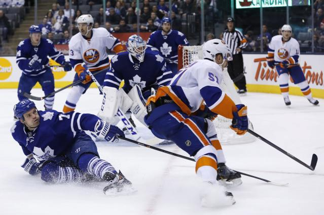 Toronto Maple Leafs' David Clarkson, left, defends against New York Islanders' Frans Nielsen during the third period of an NHL hockey hockey game, Tuesday, Nov. 19, 2013 in Toronto. (AP Photo/The Canadian Press, Mark Blinch)