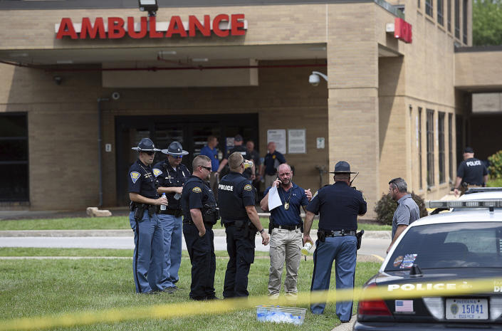 Law enforcement officers from various agencies gather outside of the ambulance entrance at Regional Hospital, Wednesday, July 7, 2021, in Terre Haute, Ind. A suspected gunman in the fatal ambush shooting of Terre Haute Police Det. Greg Ferency, left the scene and drove himself to the hospital, where he underwent surgery for his wounds, said Paul Keenan, the special agent in charge of the FBI's Indianapolis office. (Joseph C. Garza/The Tribune-Star via AP)