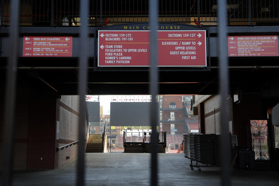 A concourse inside Busch Stadium, home of the St. Louis Cardinals baseball team, is seen through a locked gate Wednesday, March 25, 2020, in St. Louis. The start of the regular season, which was set to start on Thursday, is on hold indefinitely because of the coronavirus pandemic. (AP Photo/Jeff Roberson)