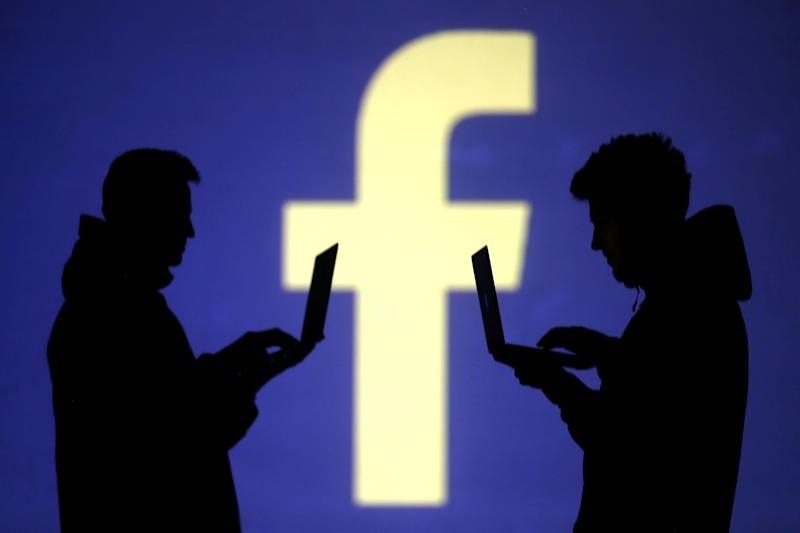 Silhouettes of laptop users are seen next to a screen projection of Facebook logo in this picture illustration taken March 28, 2018. REUTERS/Dado Ruvic/Illustration