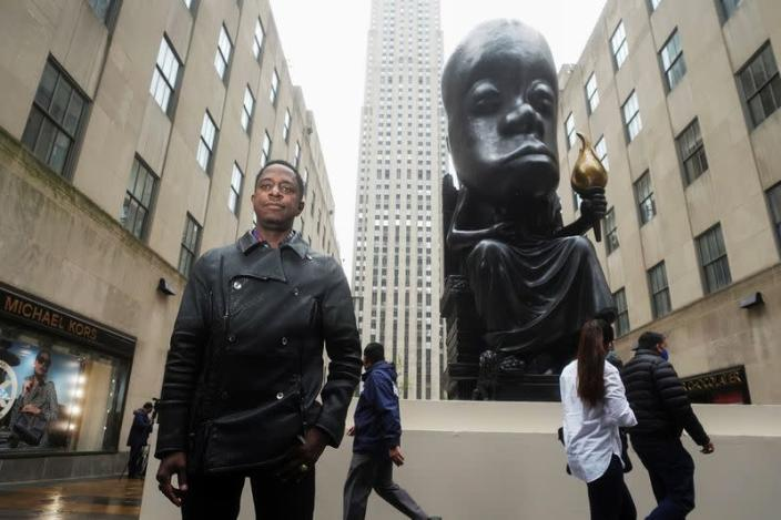 Sanford Biggers poses for a photo in front of his statue 'Oracle' in New York City