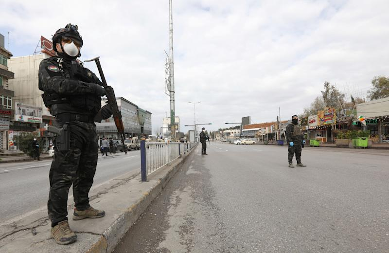 Security men stand in an empty street during a curfew imposed by Iraqi Kurdish authorities, following the outbreak of coronavirus, in Sulaimaniya, in Iraqi Kurdistan, lraq March 14. 2020. REUTERS/Ako Rasheed