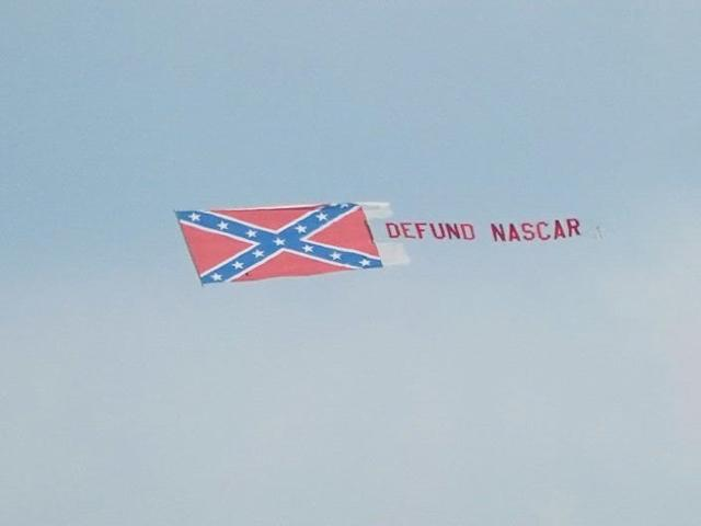 """A plane toting a Confederate flag and a banner that read """"Defund NASCAR"""" flies over the Talladega Superspeedway."""