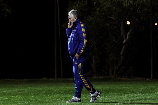 Ukrainian national soccer team coach Mykhailo Fomenko speaks on his mobile phone during a training session at the Ayia Napa resort, southeastern Cyprus, Thursday, March 4, 2014. Ukraine will face the United States in a friendly soccer match on Wednesday in Cyprus, after the match was moved from Kharkiv, Ukraine to Larnaca for security reasons. (AP Photo/Petros Karadjias)