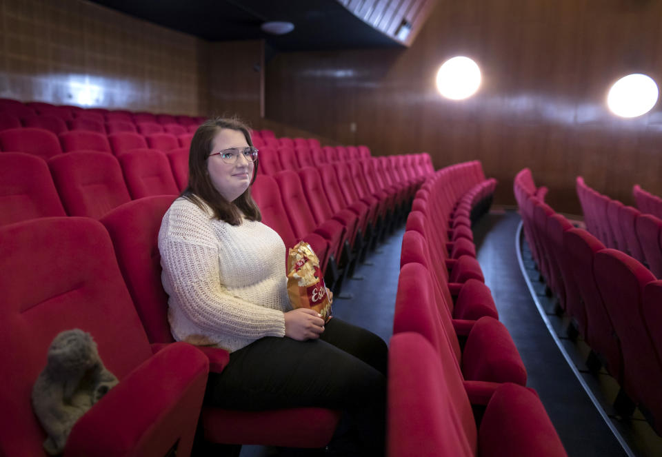 Malin Hellberg, sits alone to watch the film Tigrar, in Gothenburg, Sweden, on Saturday, Jan. 30, 2021. The 44th Goteborg film festival opened this weekend in a mostly virtual format. For the real world movie experience, a lottery determines who gets the one ticket for the 700-seat cinema. (AP Photo/Thomas Johansson)
