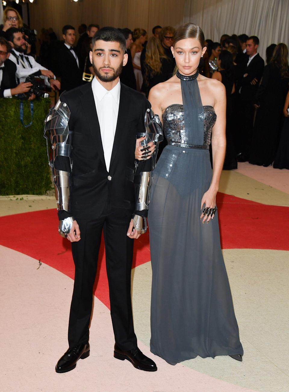 Zayn Malik stands in a suit and Gigi Hadid holds his arm wearing a grey dress on a red carpet.