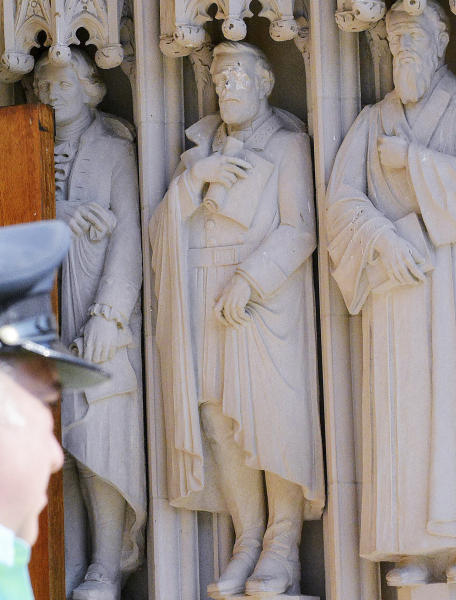 FILE - In this Aug. 17, 2017 file photo, the defaced Gen. Robert E. Lee statue, center, stands at the Duke Chapel in Durham, N.C. Duke Duke University removed a statue of Gen. Robert E. Lee early Saturday, Aug. 19, days after it was vandalized amid a national debate about monuments to the Confederacy. The university said it removed the carved limestone likeness early Saturday morning from Duke Chapel where it stood among 10 historical figures depicted in the entryway (Bernard Thomas/The Herald-Sun via AP, File)