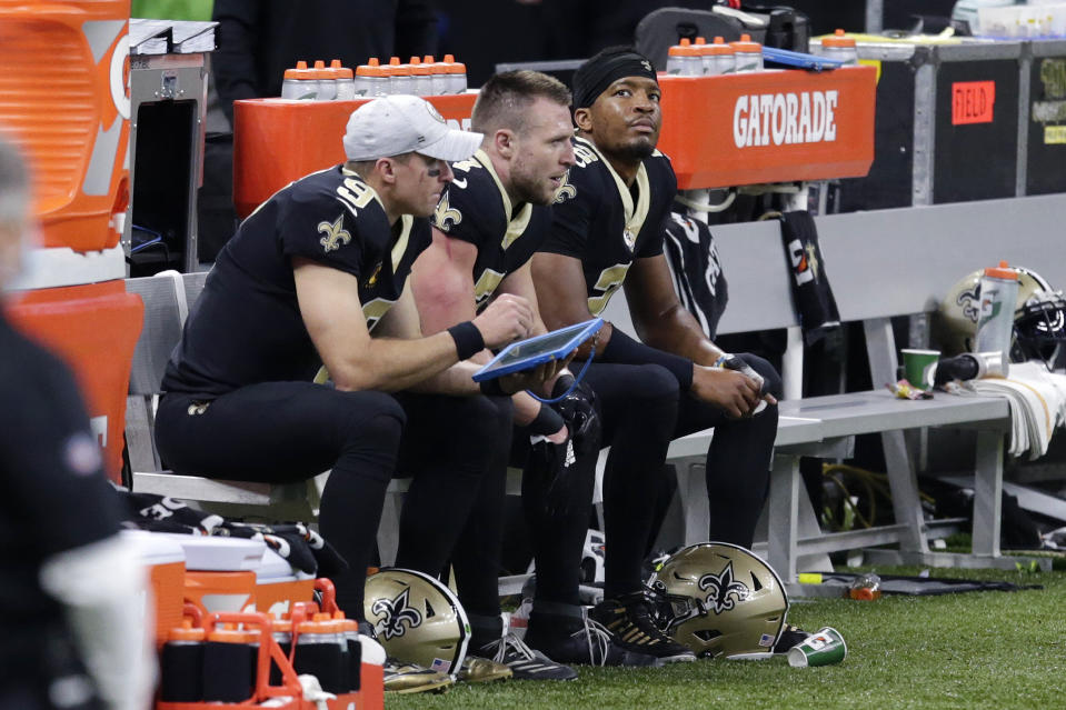 New Orleans Saints quarterbacks Drew Brees (9), Taysom Hill (7) and Jameis Winston (2), sit together on the bench in the second half of an NFL football game against the San Francisco 49ers in New Orleans, Sunday, Nov. 15, 2020. (AP Photo/Butch Dill)