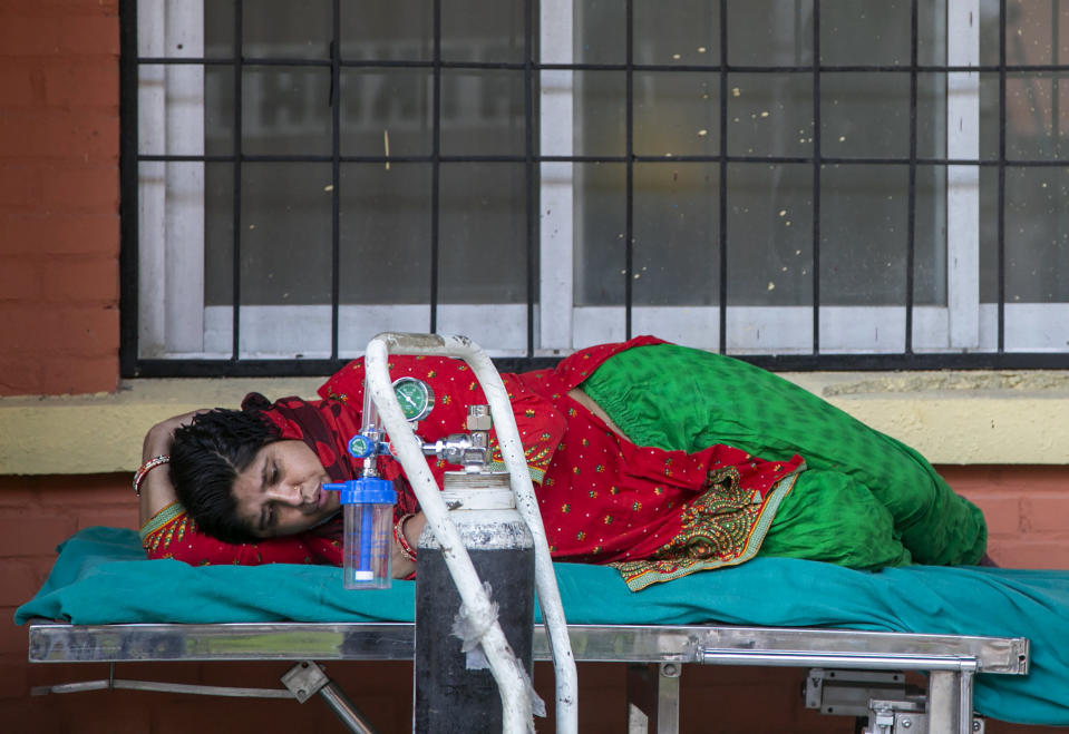 A COVID-19 patient waits to receive oxygen outside an emergency ward of a hospital in Kathmandu, Nepal, Thursday, May 6, 2021. Nepal's main cities and towns including the capital Kathmandu has been in lockdown since last month as the number coronavirus cases and deaths continue to rise. (AP Photo/Niranjan Shrestha)