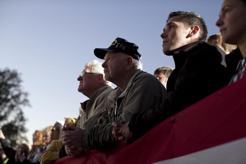 Supporters of Republican presidential candidate, former Massachusetts Gov. Mitt Romney look on as he speaks during a campaign rally at the Shelby County Fairgrounds on Wednesday, Oct. 10, 2012 in Sidney, Ohio. (AP Photo/ Evan Vucci)