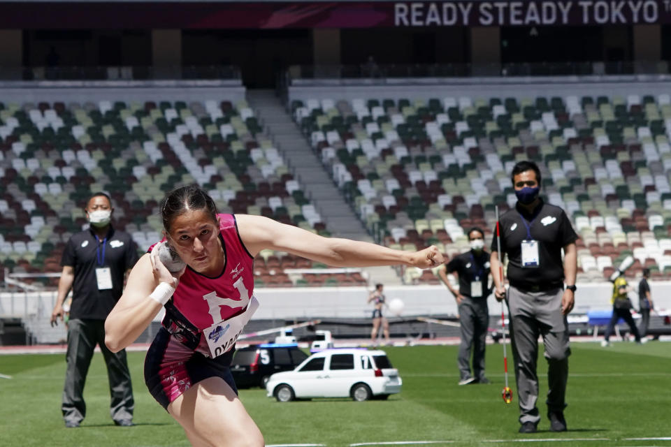 Officials, wearing face masks, look at a shot put by a Japanese competitor during an athletics test event for the Tokyo 2020 Olympics Games at National Stadium in Tokyo, Sunday, May 9, 2021. (AP Photo/Shuji Kajiyama)