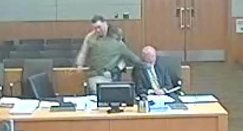 A still from the Arizona courtroom video appears to show defendant Lamont Payne punching his own lawyer (seated right) during a hearing.