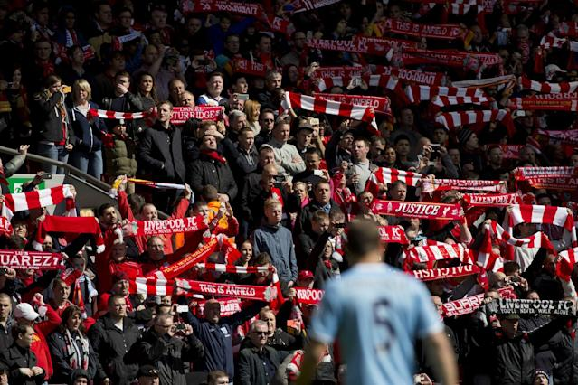 Before their English Premier League soccer match at Anfield Stadium against Manchester City Liverpool supporters hold their scarves prior to a minute's silence in tribute to the 96 supporters who lost their lives in the Hillsborough disaster of 25 years ago on 15 April 1989, Liverpool, England, Sunday April 13, 2014. (AP Photo/Jon Super)