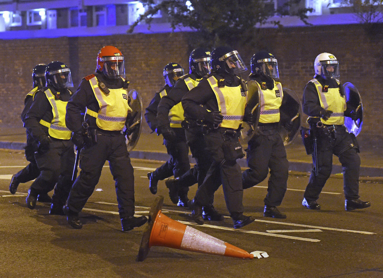 Riot police move in to quell a protest on a main street in London, late Friday, July 28, 2017. Protesters angry over the death of a young black man following a police chase have clashed with riot police in London, throwing bottles and fireworks and setting garbage cans on fire. (Lauren Hurley/PA Wire via AP)
