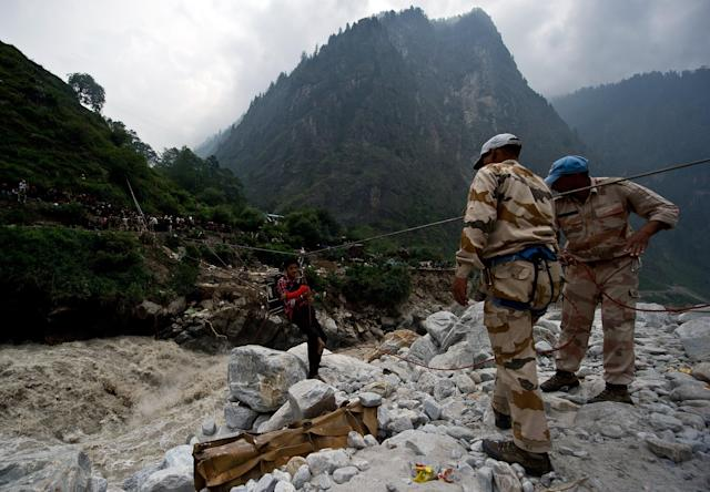 A stranded Indian pilgrim is transported across a river using a rope rescue system by Indo-Tibetan Border Police (ITBP) personnel in Govind Ghat on June 23, 2013. Bad weather hampered rescue operations June 23 in northern India where up to 1,000 people are feared to have died in landslides and flash floods that have left pilgrims and tourists stranded without food or water. AFP PHOTO/MANAN VATSYAYANA
