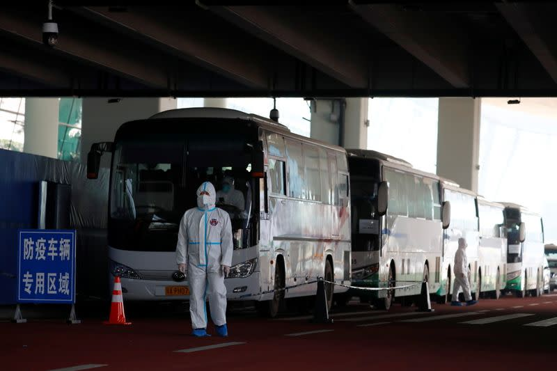 Staff member in protective suit stands next to buses before the expected arrival of a World Health Organisation (WHO) team in Wuhan