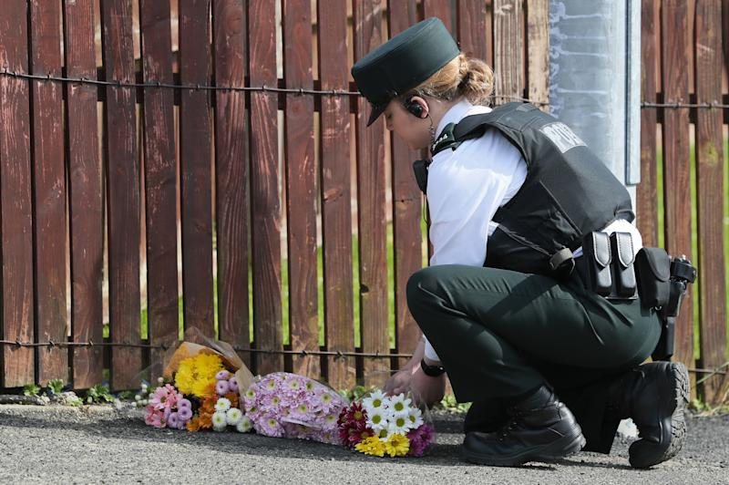 A police officer lays flowers at the scene in Londonderry, Northern Ireland, following the death of 29-year-old journalist Lyra McKee who was shot and killed when guns were fired and petrol bombs were thrown in what police are treating as a 'terrorist incident'. (Photo by Brian Lawless/PA Images via Getty Images)
