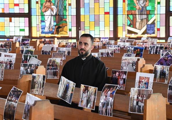Father Tony Sarkis sits in a pew amongst images of his congregation attached to them at Our Lady of Lebanon Co-Cathedral, Harris Park in Sydney.