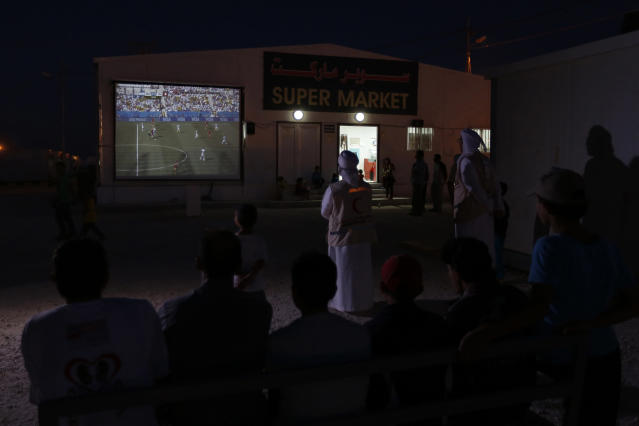 United Arab Emirates Red Crescent members and Syrian refugees watch the 2014 World Cup round of 16 soccer match between Argentina and Switzerland on a large screen after taking their meals for iftar, or the evening meal, during the Muslim fasting month of Ramadan at the Mrajeeb Al Fhood refugee camp, east of Zarqa, July 1, 2014. The camp, funded by the UAE, has received about 5,000 Syrian refugees so far, according to the Red Crescent Society of the United Arab Emirates. REUTERS/Muhammad Hamed (JORDAN - Tags: SOCIETY IMMIGRATION RELIGION SPORT SOCCER WORLD CUP CONFLICT)